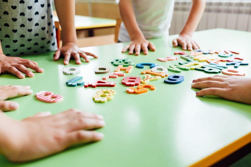 lettres colorées avec enfants autour d'une table verte