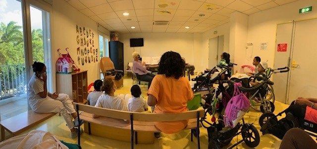 Photo d'enfants malades assis qui écoutent la lecture faite par une bibliothécaire