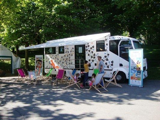 Photographie du Médiabus installé avec son auvent et des enfants qui jouent dans les transats