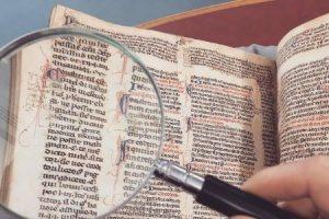 Photo d'une loupe tenue au-dessus d'un manuscrit pour mieux lire ce qui y est écrit
