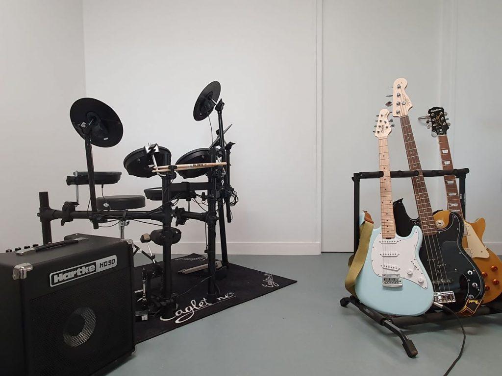 Photographie du studio de musique avec une batterie et trois guitares électriques