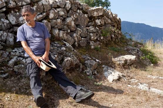 Edmond Baudoin, assis sur un mur de pierres