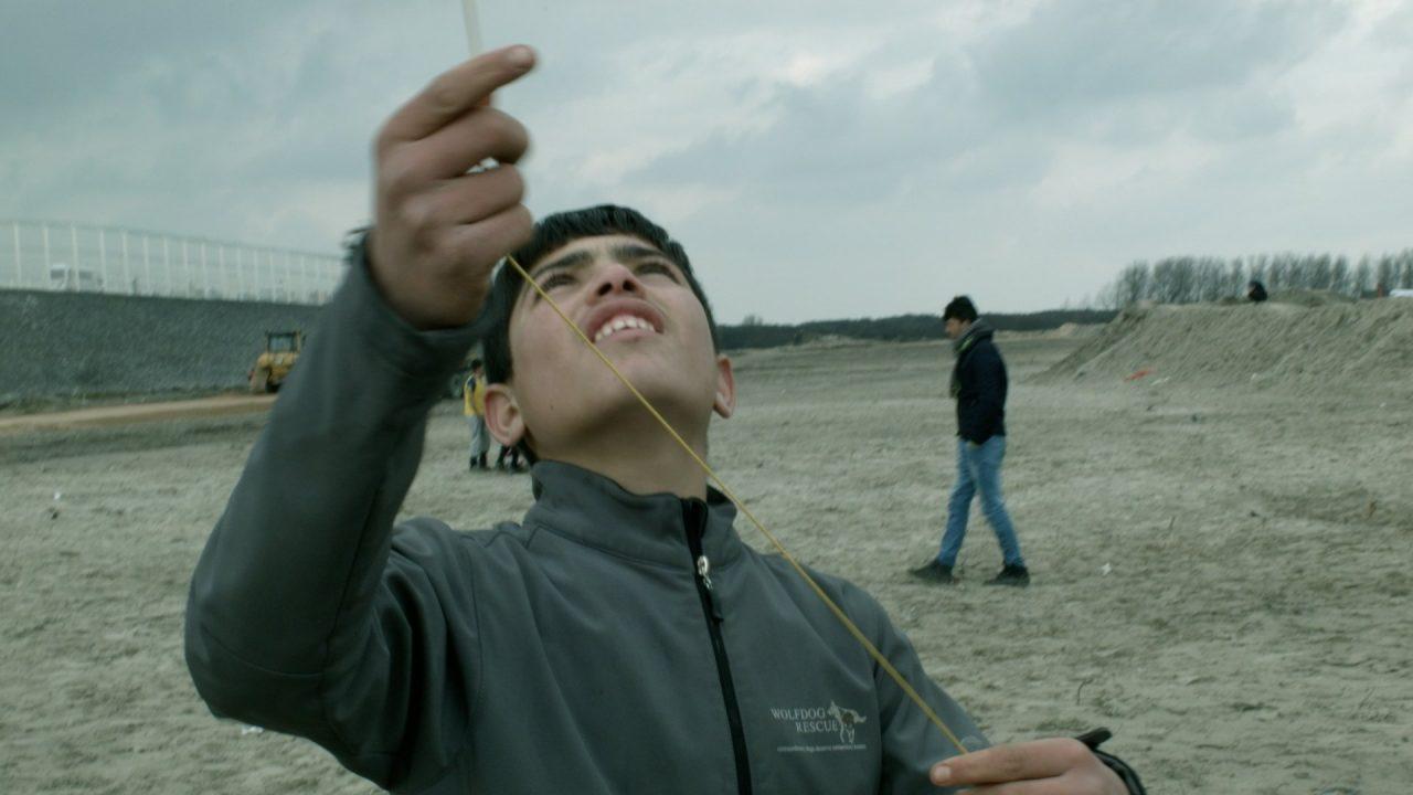 Un garçon jouant au cerf-volant dans la Jungle de Calais