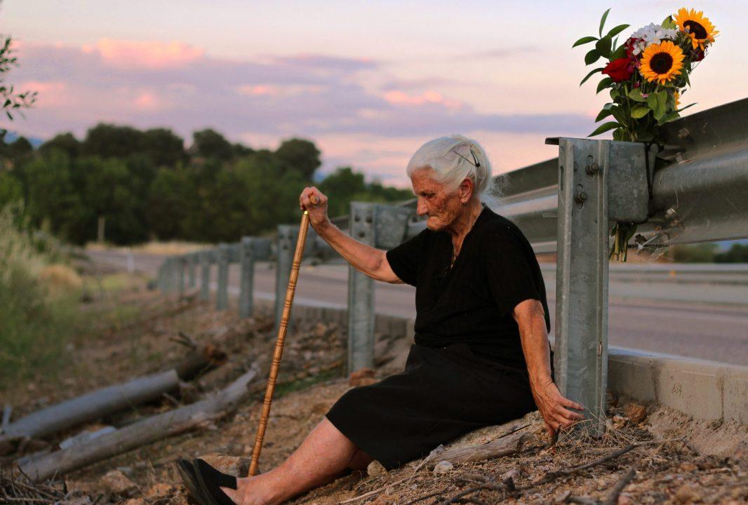 Une vieille femme assise sur le bord d'une route - Photographie du film Le Silence des autres