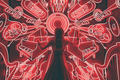 visuel représentant une femme entourée de multiples instruments sur un fonds rouge.