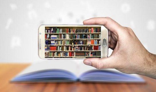 main tenant un smartphone avec une bibliothèque comme fond d'écran