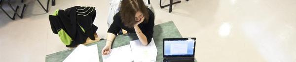 Vue en contre plongée d'une étudiante à sa table de travail