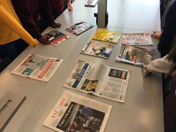 Présentation de unes de journaux et magazines sur une table de la Bpi