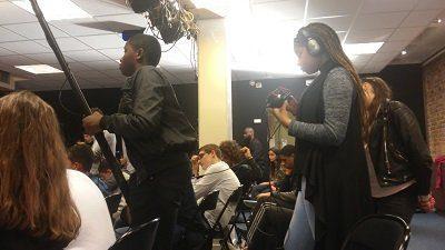 Photographie de jeunes collégiens durant le tournage de l'émission : l'un tenant une perche avec micro, l'autre enregistrant.