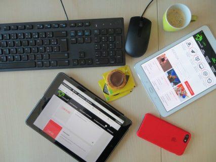 Photographie d'une tablette, d'un téléphone portable et d'une souris disposés sur une table
