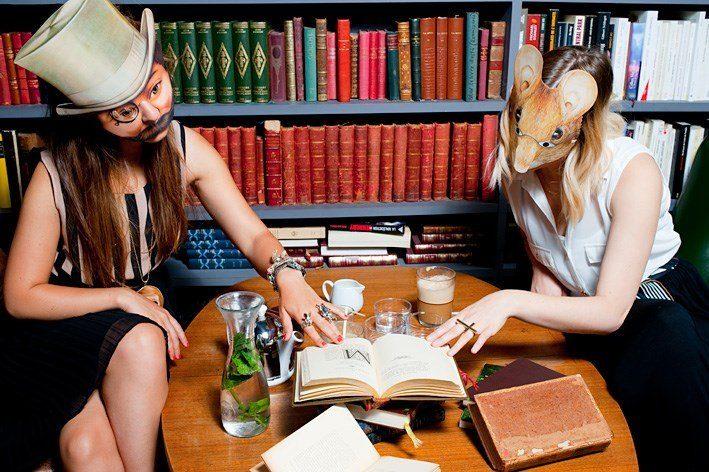 Photographie de deux femmes masquées lisant le même livre devant une bibliothèque