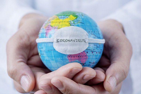 deux mains portant une balle représentant la terre cernée par un élastique portant le mot coronavirus