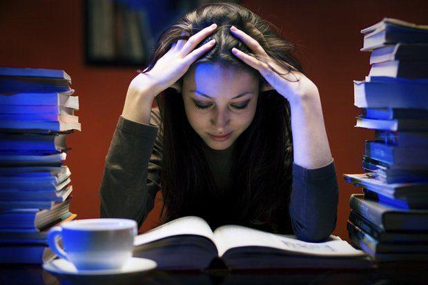 Photo représentant une jeune femme assise en train de lire en se tenant la tête à deux mains.