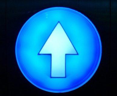 Flèche vers le haut inscrite dans un cercle lumineux