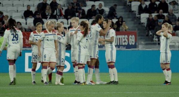 photo représentant l'équipe féminine de football de Lyon sur le terrain en train d'échanger.