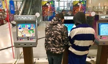 Photographie de jeunes de dos jouant sur des consoles de jeux vidéos