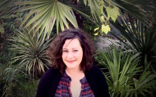 Portrait de la réalisatrice Amélie Harrault devant des feuilles de palmier