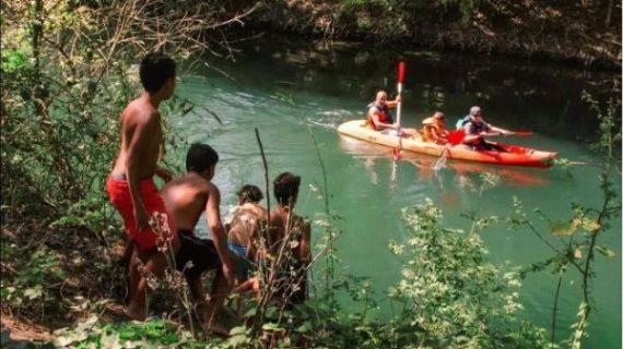 Image du documentaire avec un groupe d'enfants sur la rive d'un ruisseau sur lequel passe trois personnes en kayak
