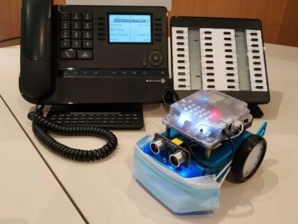 Photographie d'un téléphone avec devant un petit robot qui porte un masque