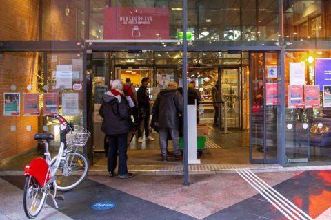Des usagers passent le portique d'une bibliothèque.
