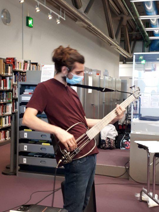 Démonstration de basse vibratoire : l'instrument est composé d'un manche et cordes de basse supportés par une tige de fer arrondie qui repose sur les hanches et le ventre.