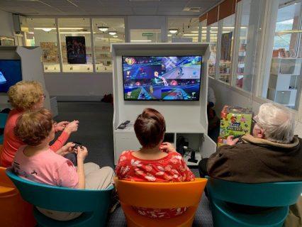 Photographie d'un groupe de trois seniors qui jouent assis à un jeu vidéo