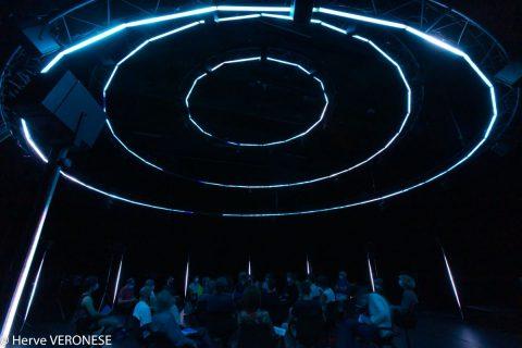 Photographie d'un dôme sous lequel sont assises vingt personnes qui écoutent la lecture d'un texte