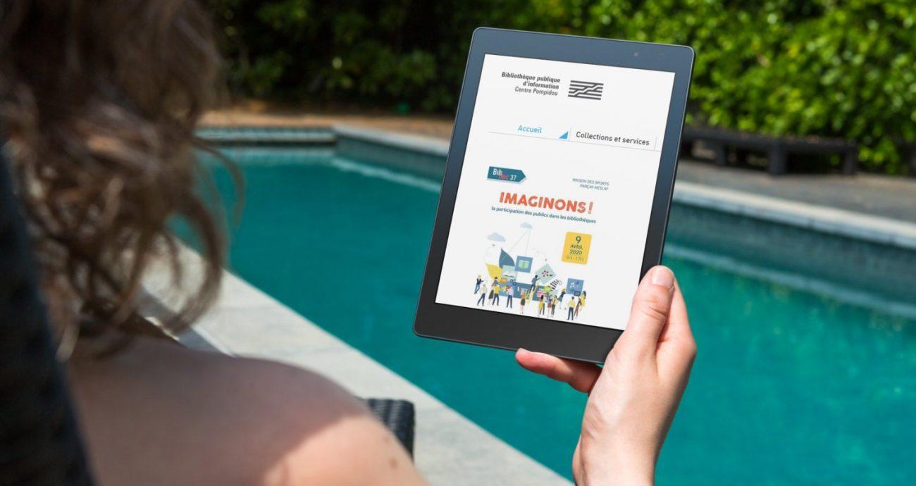 Photographie d'une femme qui regarde le site Bpi pour les professionnels sur une tablette au bord d'une piscine